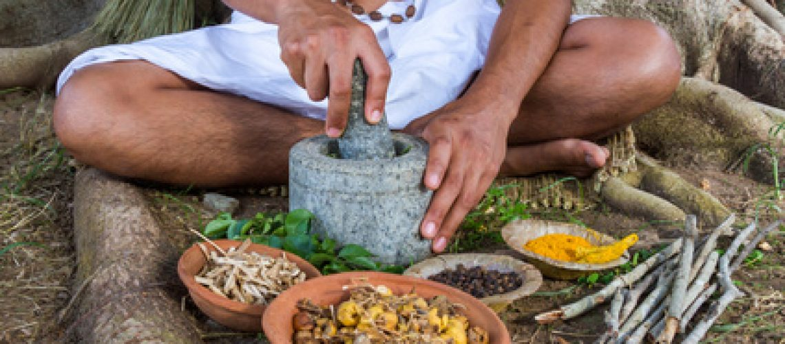 A young man preparing ayurvedic medicine in the traditional manner in India